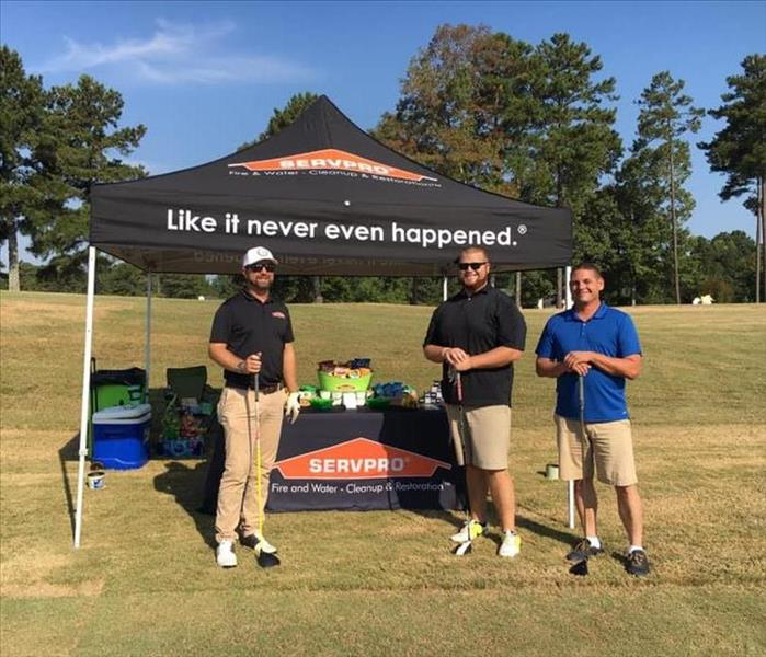Three guys standing in front of our SERVPRO tent at a golf tournament